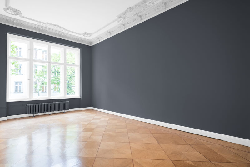 An empty room, big window, wooden floor and freshly painted dark grey walls.