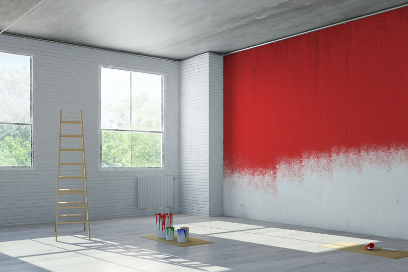 A room that is being decorated and a wall that is being painted with red paint.
