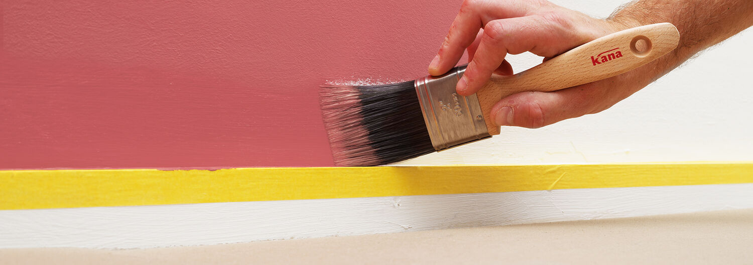 Kana paint brush is used to paint a smooth line on the wall above skirting board.