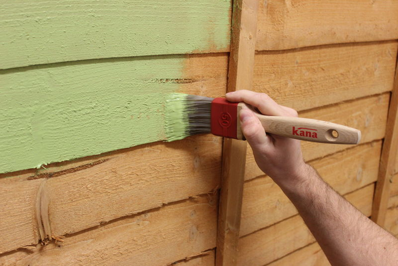 Closeup of a wooden fence being painted with a paint brush.