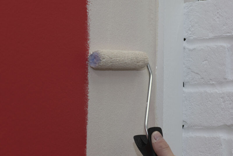A mini paint roller being used to paint a wall white.